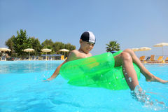 Boy sits on an inflatable arm-chair in pool. Boy sits on an inflatable arm-chair in  pool under open-skies and floats Royalty Free Stock Photos