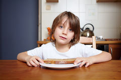 Boy sits at kitchen table and doesn't want to eat Stock Photo