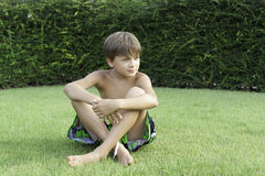 The boy sits on a lawn Stock Photos