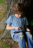 Boy sits leaning against a trunk of big old tree and looks at the tablet screen. The boy sits leaning against a trunk of a big old tree and looks at the tablet Royalty Free Stock Image