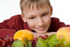 Boy sits and looks at the fruits Stock Image