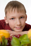 Boy sits and looks at the fruits Royalty Free Stock Photography