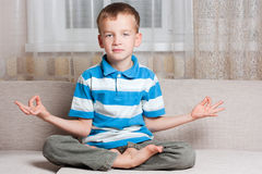 Boy sits in a lotus position. Royalty Free Stock Photography