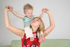 Boy sits on mother shoulders Royalty Free Stock Photos