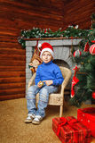 Boy sits near Christmas tree and gifts Stock Images