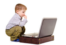Boy sits at a notebook. Little boy thoughtfully sits at a notebook Royalty Free Stock Photos
