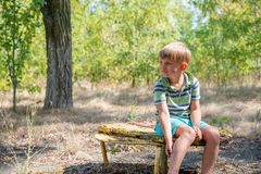 The boy sits on an old bench, in an abandoned park and looks around with a sad face. The boy sits on an old bench, in an abandoned park and looks around with a royalty free stock image