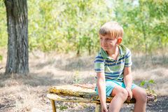 The boy sits on an old bench, in an abandoned park and looks around with a sad face. The boy sits on an old bench, in an abandoned park and looks around with a stock photo