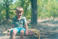The boy sits on an old bench, in an abandoned park and looks around with a sad face. The boy sits on an old bench, in an abandoned park and looks around with a stock photography