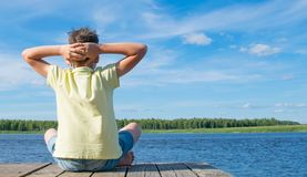 The boy sits on the pier, stretches and breathes air, against the lake, on the right there is a place for the inscription stock images