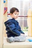 Boy sits on playground Stock Image