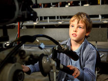 Boy sits on professional camera Stock Photo