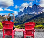 Boy sits in a red lounge chair and photographs stock photos