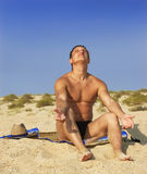 Boy sits on sand and blinks the eyes Royalty Free Stock Image