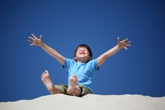 Boy sits on sand with lifted hands Stock Photo