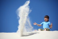 Boy sits on sand and scatters it Stock Photography