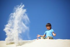 Boy sits on sand and scatters it Stock Photos