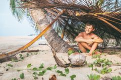 Boy sits in selfmade hut on the tropical beach and plays in Robi Royalty Free Stock Image