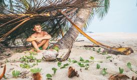 Boy sits in selfmade hut on the tropical beach and plays in Robi. Nzone Royalty Free Stock Photography