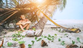 Boy sits in selfmade hut on the tropical beach and plays in Robinzone royalty free stock photos