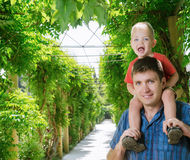 Boy sits on shoulder beside father Royalty Free Stock Photography
