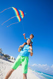 Boy sits on shoulders of dad holding flying kite Royalty Free Stock Photo