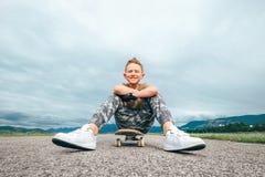 Boy sits on skate board Stock Photo