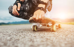 Boy sits on the skateboard legs and hands closeup image Royalty Free Stock Photos