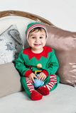 A boy sits in a sled. Little boy in elf costume sitting in the chair at a home interior by the fireplace and waiting for Santa Stock Photo