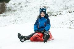 A boy sits on sledge Royalty Free Stock Photos