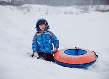 The boy sits in the snow , holding the tubing Royalty Free Stock Images