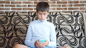 Boy sits on the sofa in his room and uses a smartphone. Modern technology in the life of children concept