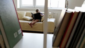 Boy sits on the sofa at home and reads some magical book with interest stock video