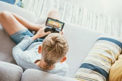 Boy sits on sofa plays with smartphone and gamepad camera top view. Child and electronic devices concept stock image