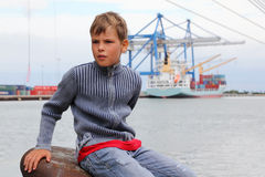 Boy sits on stone at background of ship Stock Photography