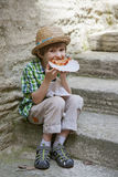 Boy sits on stone steps and eats pizza Royalty Free Stock Photos