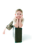 The boy sits on  suitcase Stock Images