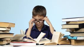 Boy sits at the table and excitedly leafing through the pages of books. Blue background. stock footage