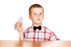 Boy sits at  table and holding  paper airplane isolated. Stock Images
