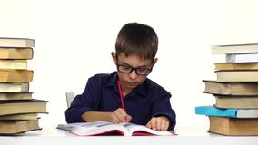 Boy sits at the table leafing through the book. White background stock video
