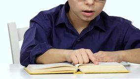 Boy sits at the table leafing through the pages of a book. White background. Close up stock footage