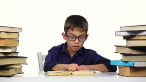 Boy sits at the table leafing through the pages of a book. White background. stock footage