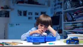 The boy sits at the table, misses. Boring boy sits at a table at school, plays with toys stock video footage