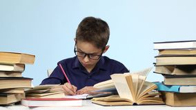Boy sits at the table and pull up a page with a notebook. Blue background. stock video footage