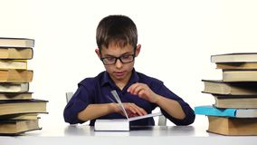 Boy sits at a table and reading a book. White background stock video