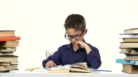 Boy sits at a table recording something into her notebook and flips through the book. White background stock video