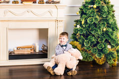 Boy sits with teddy bear in the background of the Christmas tree. Boy sits with teddy bear in the background of the Christmas tree Stock Image