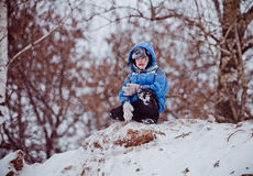 The boy sits on the top of the hill Stock Image