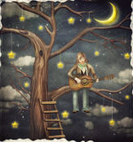 The boy sits on tree and plays  on   guitar Stock Images