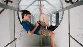 The boy sits under the bridge in the classroom metal corridor. Nice shots. The camera is in motion. Cool architecture. Atmospheric moments stock video